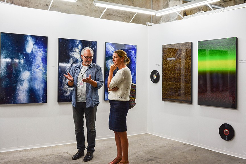 Visitors of the Discovery Art Fair discuss abstract paintings.