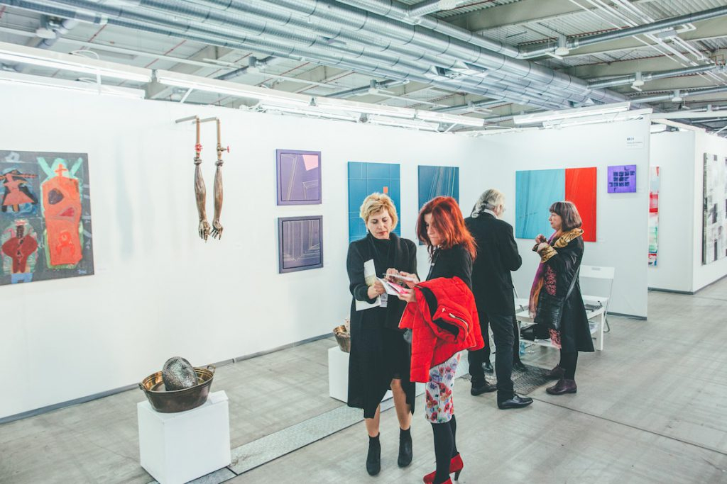 Contemporary, abstract paintings and sculptures at an exhibition space.