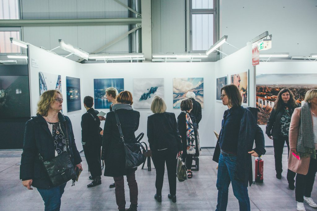 Visitors browsing a trade fair for emerging artists