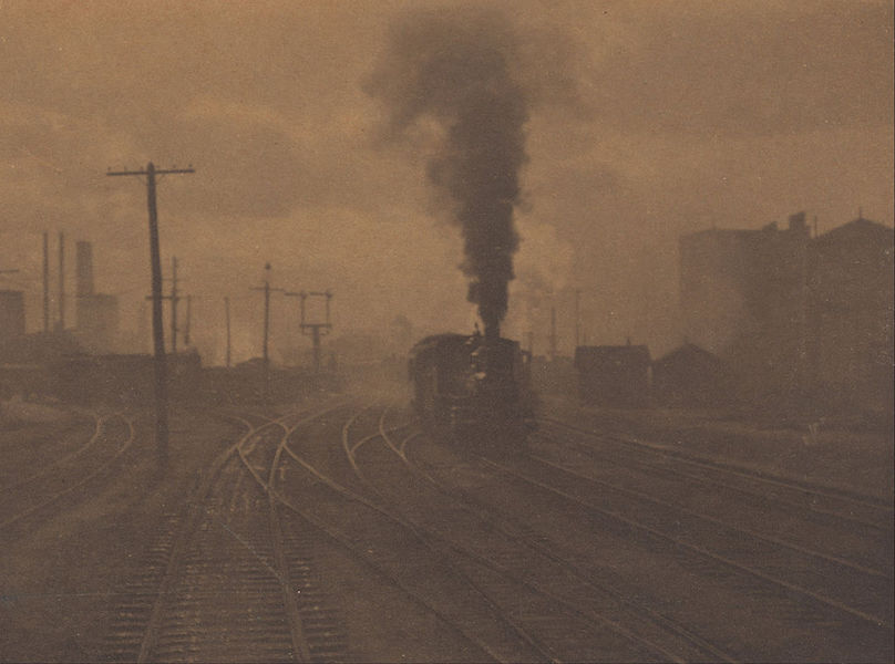 "Alfred Stieglitz ""The Hand of Man"", cityscape showing a monochromatic photo of train tracks with an approaching train."