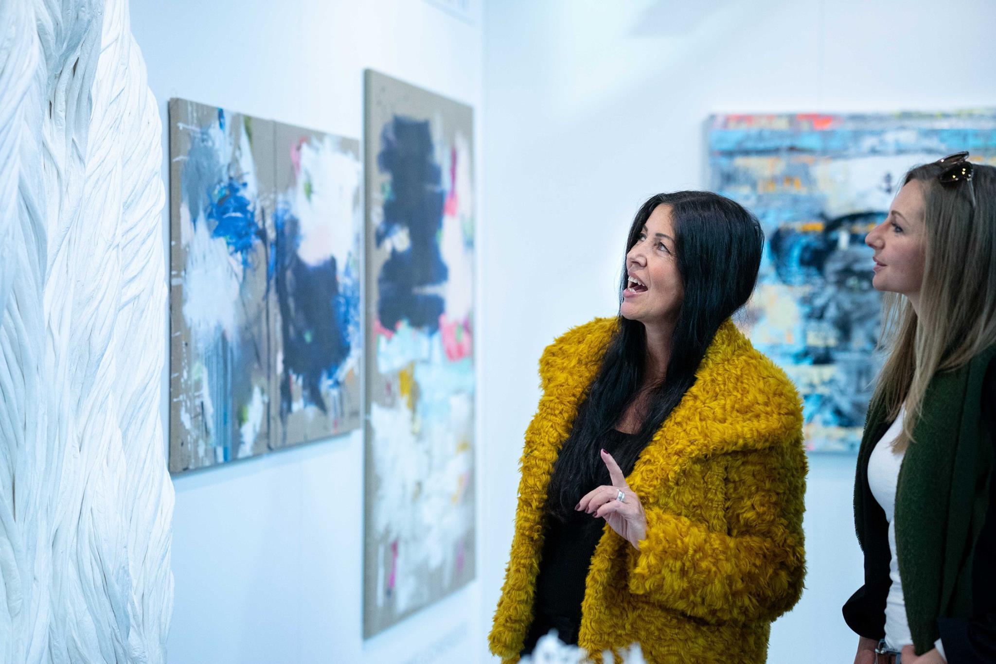 Besucher betrachten abstrakte Gemälde auf der Kunstmesse Discovery Art Fair in FFM